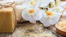 Sal de baño, orquídea y toallas en una tabla fotos de archivo libres de regalías
