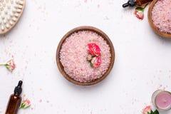 Sal de baño de Rose con las flores y las botellas de aceite naturales en el fondo blanco imágenes de archivo libres de regalías