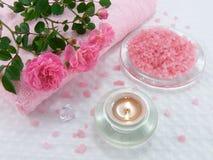 Sal de banho com petróleo cor-de-rosa, vela e rosas Fotografia de Stock