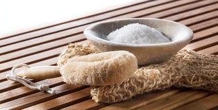Sal de banho de amaciamento na luva da bucha e escova para a desintoxicação Fotografia de Stock