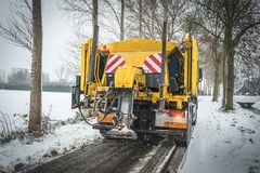Sal de espalhamento do caminhão do serviço do inverno na estrada foto de stock