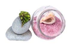 Sal del mar en un tarro de cristal, piedras y una hoja verde Imagen de archivo libre de regalías