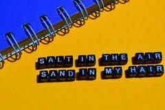 Sal en la arena del aire en mi pelo en bloques de madera concepto del negocio en fondo anaranjado imagen de archivo libre de regalías