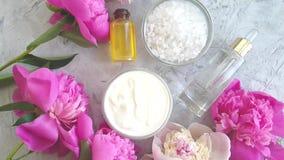 Sal natural del aceite del suero de la tabla de la peon?a del balneario cosm?tico poner crema de la flor en la c?mara lenta del f almacen de video