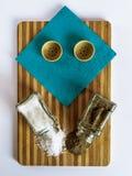 Sal y pimienta dispersadas de las coctelera de sal de cristal y de las coctelera de la pimienta en una tabla de cortar fotografía de archivo