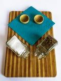 Sal y pimienta en un soporte de cristal de la coctelera y de la coctelera de la pimienta en una tabla de cortar imágenes de archivo libres de regalías