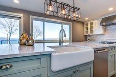 A sala bonita da cozinha com ilha verde e a exploração agrícola afundam-se fotografia de stock