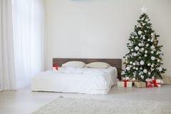 Sala branca da decoração com os presentes do Natal do ano novo da cama Fotos de Stock Royalty Free