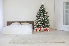Sala branca da decoração com os presentes do Natal do ano novo da cama Imagens de Stock Royalty Free