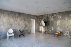 Sala clara moderna do sótão-estilo com cadeiras e iluminação do desenhista Paredes cinzentas com a textura do concreto De madeira imagens de stock royalty free