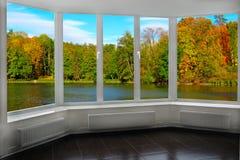 Sala com a janela com vista à floresta e ao lago do outono Paisagem outonal fotos de stock