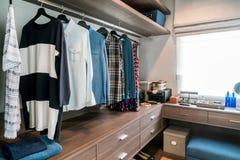 Sala com prateleiras de madeira e os vestidos que penduram sob a cremalheira, fotos de stock