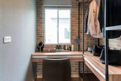 Sala com prateleiras de madeira e os vestidos que penduram sob a cremalheira, imagens de stock