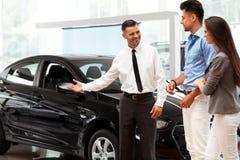 Sala d'esposizione dell'automobile Giovani coppie che comprano una nuova automobile alla gestione commerciale fotografia stock
