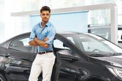 Sala d'esposizione dell'automobile Uomo felice vicino all'automobile del suo sogno fotografia stock libera da diritti