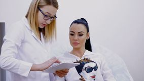 A sala da cosmetologia, duas mulheres bonitas novas, um doutor e um paciente discutem vários procedimentos cosméticos, olham filme
