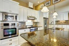 Sala da cozinha com partes superiores do granito e combinação branca do armazenamento Imagem de Stock Royalty Free