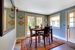 Sala da pranzo blu con la coperta rossa e l'alta tabella. Fotografia Stock