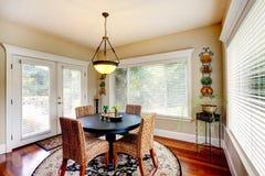 Sala da pranzo con la tavola nera rotonda e le sedie di vimini Fotografia Stock