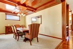 Sala da pranzo con le pareti gialle ed il soffitto di legno. fotografie stock