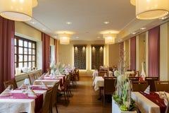 Sala da pranzo con le tavole coperte bianche Immagine Stock Libera da Diritti