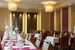 Sala da pranzo con le tavole coperte bianche Immagine Stock