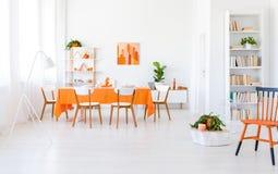 Sala da pranzo luminosa interna con la finestra, tovaglia arancio, quattro sedie fotografie stock libere da diritti