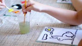 A sala de aula do desenho, close-up, mãos do ` s das crianças lava em um vidro um pincel para tirar a menina tira com cores, mest vídeos de arquivo
