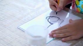 Sala de aula do desenho, close-up, mãos do ` s das crianças a menina tira esboços com pintura preta, tira um coelho, domina vídeos de arquivo