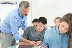 Sala de aula de Explaining Students In do professor fotos de stock