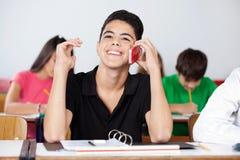 Sala de clase adolescente de Using Phone In del estudiante masculino Imagen de archivo