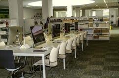 Sala de clase con luz del día superior, lugares de trabajo individuales, sillas y tablas con los ordenadores en la universidad in fotos de archivo