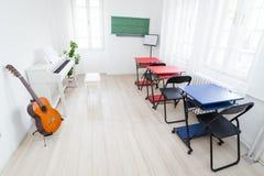 Sala de clase moderna de la luz del día para la música de enseñanza Guitarra, pian blanco imagen de archivo libre de regalías