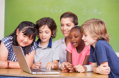 Sala de clase primaria interracial que aprende utilizar el ordenador portátil con su Fotografía de archivo libre de regalías