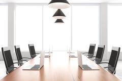 Sala de conferencias moderna con muebles, ordenadores portátiles y ventanas grandes Fotos de archivo libres de regalías