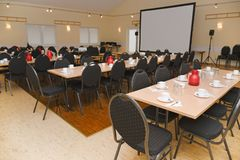Sala de conferencias vacía con la pantalla de proyección, las tablas determinadas y las sillas fotografía de archivo libre de regalías