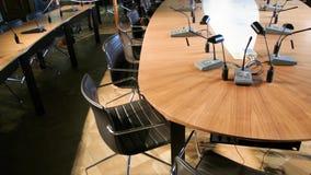 Sala de conferencias vacía con los micrófonos y tablas y asientos de madera