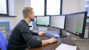 Sala de control, trabajador el operador de la producción del control del tablero de instrumentos en el cuarto del comando