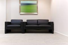 Sala de espera de la oficina con la silla de cuero y el sofá negros Imagen de archivo