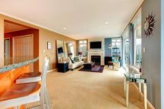 Sala de estar abierta grande de la ensenada con la chimenea, la TV y muebles modernos. Imágenes de archivo libres de regalías