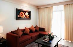 Sala de estar acogedora con la pared moderna de la pintura decorativa y roja tan fotografía de archivo