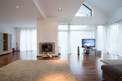 Sala de estar acogedora con las ventanas y la chimenea grandes Imágenes de archivo libres de regalías