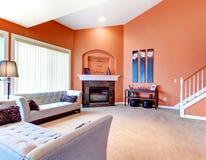 Sala de estar anaranjada maravillosa con el sofá clásico gris, oscuridad empedrado Imágenes de archivo libres de regalías