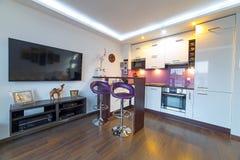 Sala de estar blanca moderna con la cocina Imágenes de archivo libres de regalías
