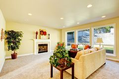 Sala de estar brillante con la chimenea y el sofá beige Fotografía de archivo libre de regalías