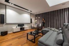 Sala de estar con la pantalla de proyector imagen de archivo libre de regalías