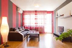 Sala de estar con las paredes rayadas negras y rojas foto de archivo libre de regalías