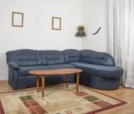 Sala de estar con un sofá y una pequeña tabla foto de archivo libre de regalías