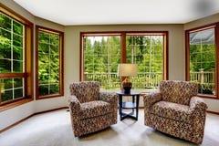 Sala de estar de la comodidad con las ventanas francesas grandes Imagen de archivo libre de regalías
