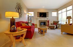 Sala de estar elegante con el sofá rojo, chimenea imagen de archivo